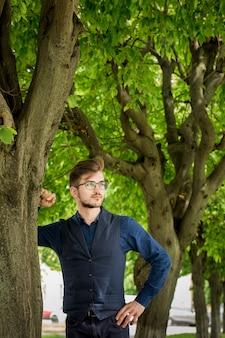 Jovem bonito com uma barba no parque debaixo da árvore