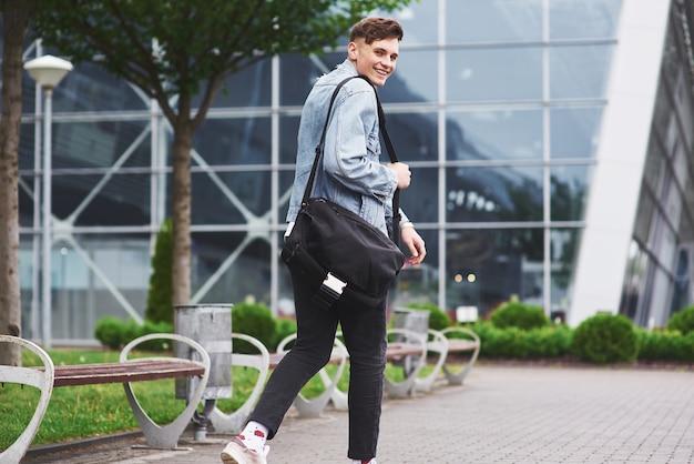 Jovem bonito com uma bolsa no ombro com pressa para o aeroporto.