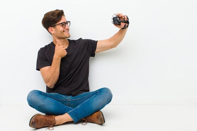 Jovem bonito com uma câmera vintage, sentada no chão, sentada no chão em uma sala branca