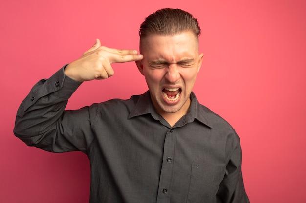 Jovem bonito com uma camisa cinza fazendo um gesto de pistola perto de sua têmpora, gritando louco de raiva em pé sobre uma parede rosa