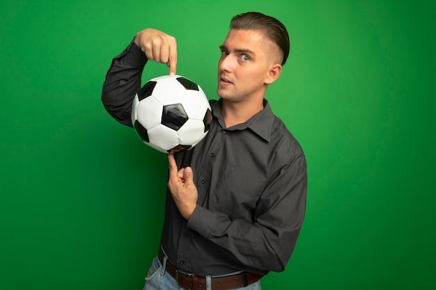 Jovem bonito com uma camisa cinza mostrando uma bola de futebol apontando com o dedo indicador para ela e sorrindo confiante em pé sobre a parede verde