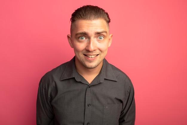 Jovem bonito com uma camisa cinza olhando para a frente sorrindo com uma cara feliz em pé sobre a parede rosa
