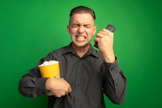 Jovem bonito com uma camisa cinza segurando um balde com pipoca usando o controle remoto da tv gritando louco louco e frustrado em pé sobre a parede verde