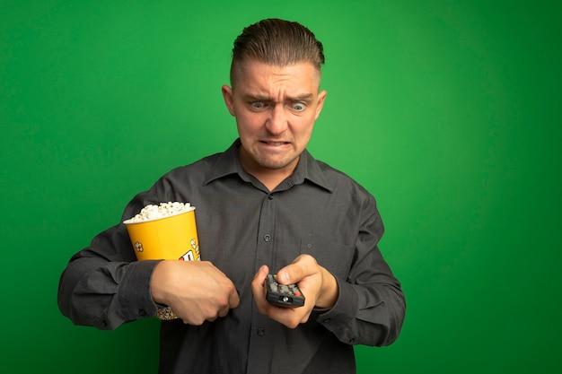 Jovem bonito com uma camisa cinza segurando um balde com pipoca usando o controle remoto da tv, olhando para ele com cara de raiva enlouquecendo de pé sobre a parede verde