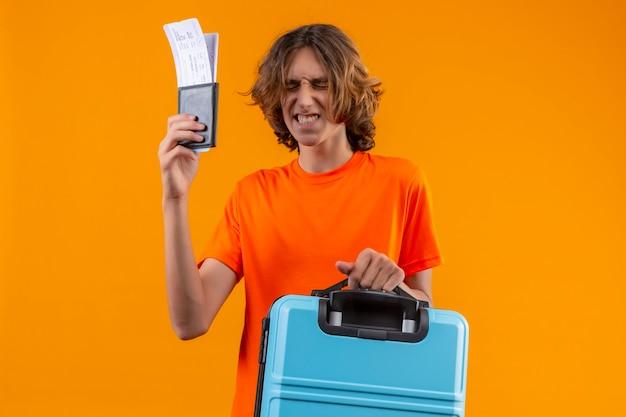 Jovem bonito com uma camiseta laranja segurando uma mala de viagem e passagens aéreas em pé com os olhos fechados fazendo um desejo desejável sobre fundo amarelo