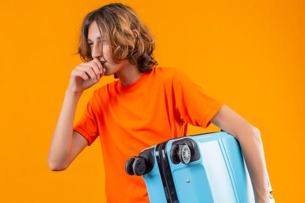 Jovem bonito com uma camiseta laranja segurando uma mala de viagem olhando de lado e sorrindo confiante em pé sobre um fundo amarelo