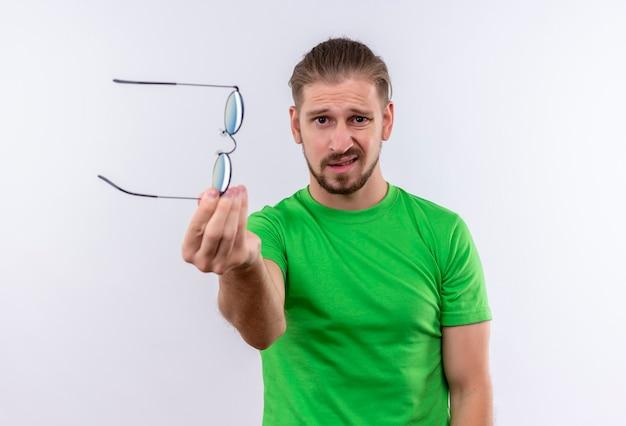 Jovem bonito com uma camiseta verde segurando os óculos e mostrando para a câmera com uma expressão cética em pé sobre um fundo branco