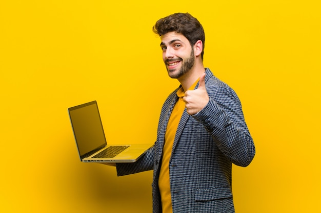 Jovem bonito com uma laranja de laptop