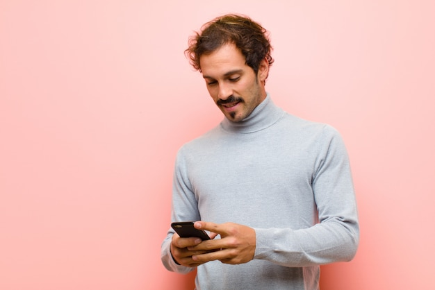 Jovem bonito com uma parede plana de telefone inteligente rosa