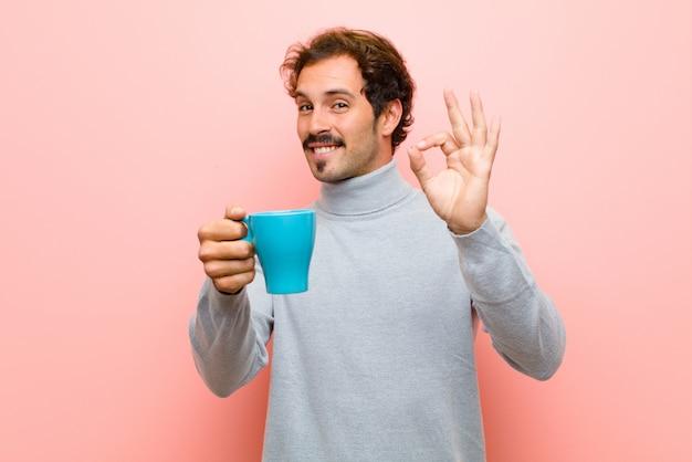 Jovem bonito com uma parede plana de xícara de café-de-rosa