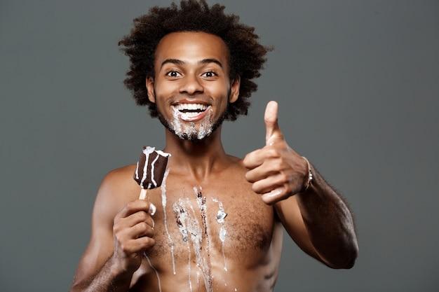 Jovem bonito comendo sorvete sobre parede cinza
