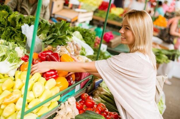 Jovem bonito comprando legumes no mercado