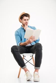 Jovem bonito concentrado de chapéu sentado e lendo um livro