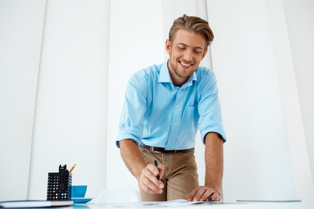 Jovem bonito confiante alegre sorridente empresário trabalhando em pé no esboço de desenho de mesa. interior de escritório moderno branco