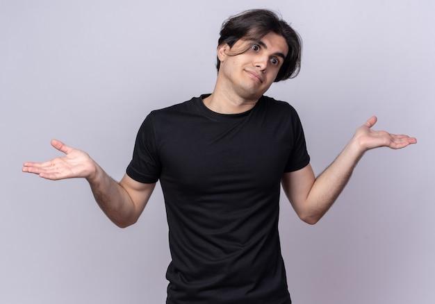 Jovem bonito confuso, inclinando a cabeça e vestindo uma camiseta preta, estendendo as mãos isoladas na parede branca