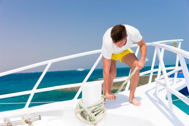 Jovem bonito conserta corda em iate em um dia ensolarado de verão, lindo mar no fundo
