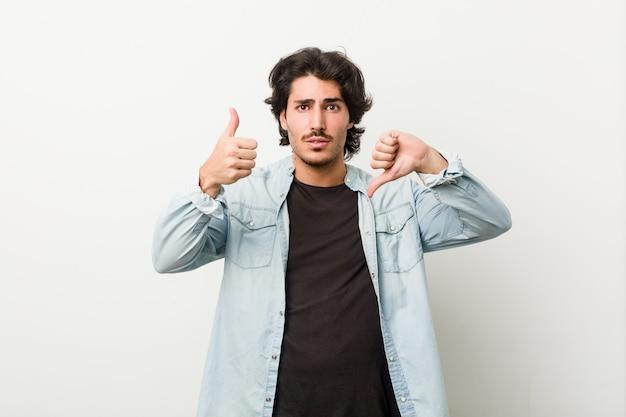 Jovem bonito contra uma parede branca, mostrando os polegares para cima e os polegares para baixo, difícil escolher o conceito