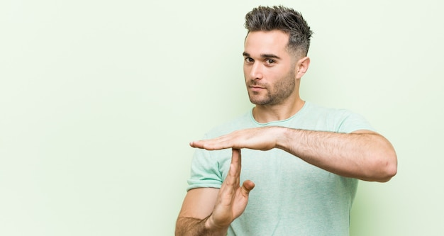 Jovem bonito contra uma parede verde, mostrando um gesto de tempo limite.