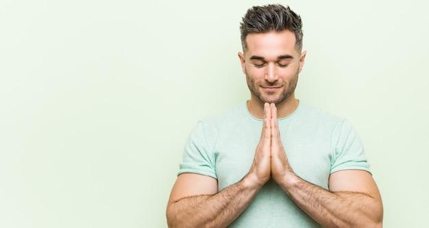 Jovem bonito contra uma parede verde, segurando as mãos em rezar perto da boca, sente-se confiante.