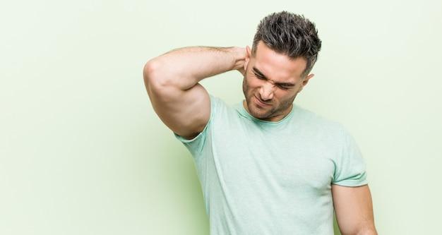 Jovem bonito contra uma parede verde, sofrendo dores no pescoço devido ao estilo de vida sedentário.