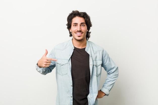 Jovem bonito contra uma pessoa de parede branca, apontando à mão para um espaço de cópia de camisa, orgulhoso e confiante