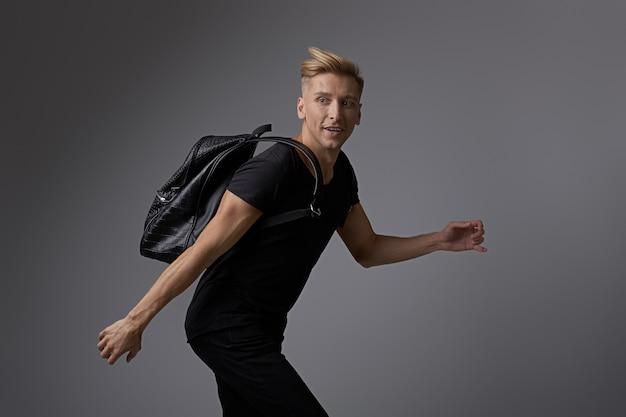 Jovem bonito correndo com uma mochila nos ombros
