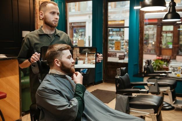 Jovem bonito cortando cabelo de barba de cabeleireiro enquanto está sentado na cadeira de barbearia.