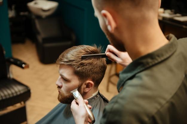 Jovem bonito cortando cabelo de cabeleireiro com navalha enquanto está sentado na cadeira de barbearia. olhe para o lado.
