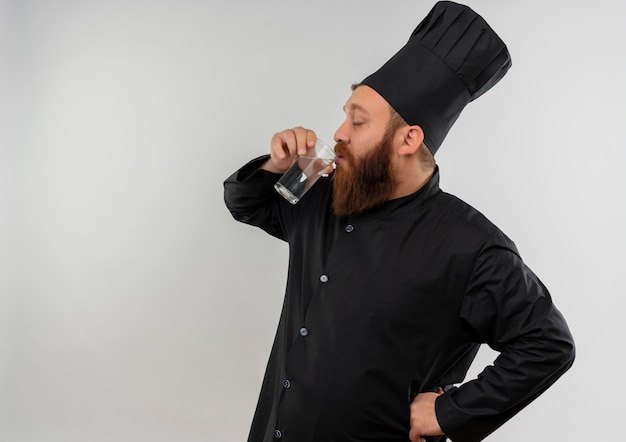 Jovem bonito cozinheiro em uniforme de chef bebendo água de vidro com a mão na cintura e os olhos fechados, isolado no espaço em branco