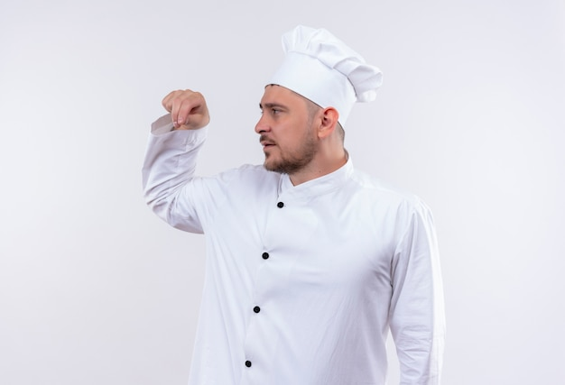 Jovem bonito cozinheiro em uniforme de chef derramando sal olhando para o lado isolado no espaço em branco