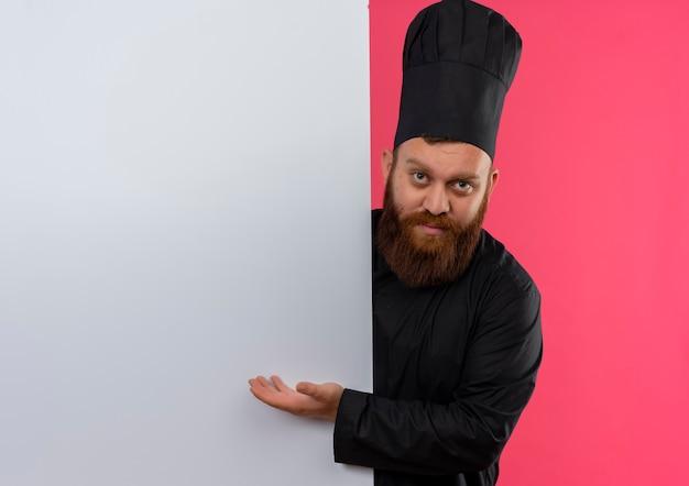 Jovem bonito cozinheiro em uniforme de chef em pé atrás de uma parede branca e apontando com a mão para ela, parecendo isolado no espaço rosa