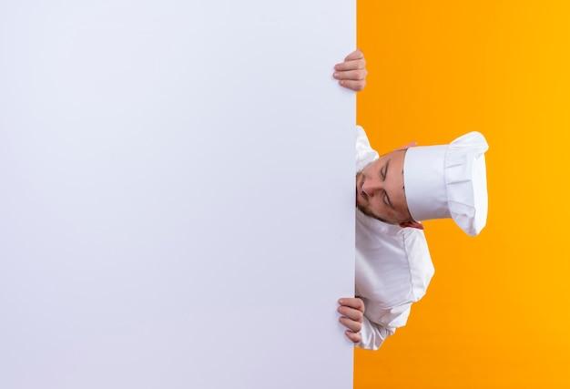 Jovem bonito cozinheiro em uniforme de chef em pé atrás de uma parede branca e olhando para ele isolado no espaço laranja
