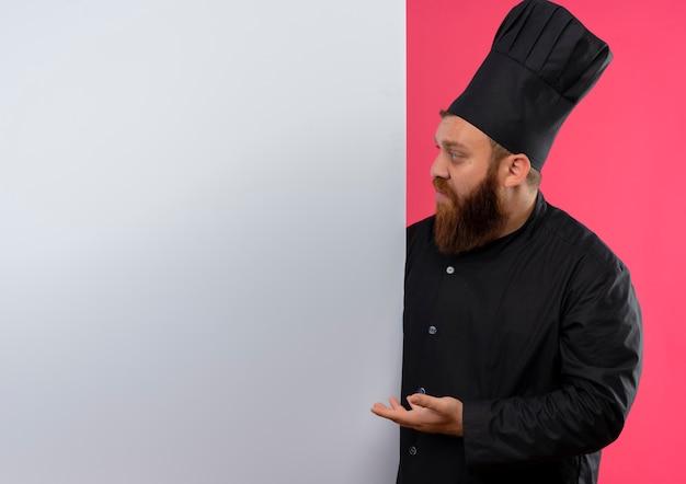Jovem bonito cozinheiro em uniforme de chef em pé atrás, olhando e apontando com a mão para uma parede branca isolada no espaço rosa