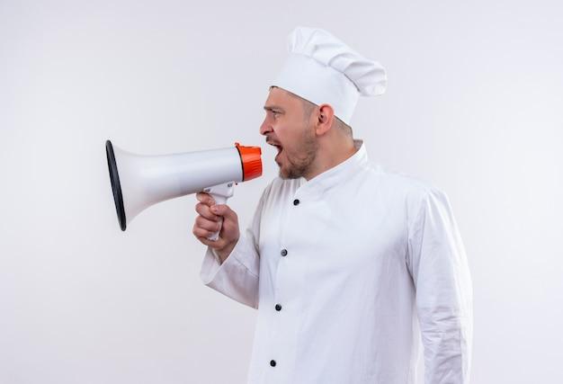 Jovem bonito cozinheiro em uniforme de chef falando por alto-falante, olhando para o lado isolado no espaço em branco