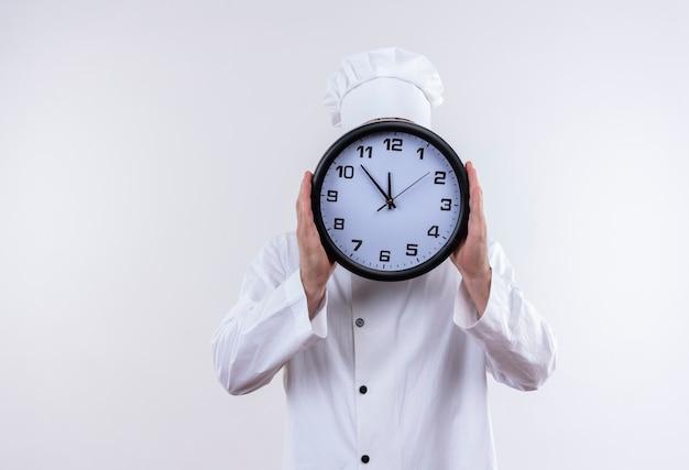 Jovem bonito cozinheiro em uniforme de chef segurando o relógio e se escondendo atrás dele, isolado no espaço em branco