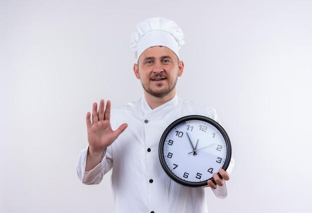 Jovem bonito cozinheiro sorridente com uniforme de chef segurando o relógio e levantando a mão, isolado no espaço em branco