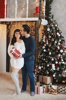 Jovem bonito dá um presente de natal para sua adorável namorada ao lado de uma árvore de natal decorada