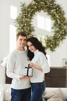 Jovem bonito dá um presente de natal para sua linda namorada com longos cabelos escuros
