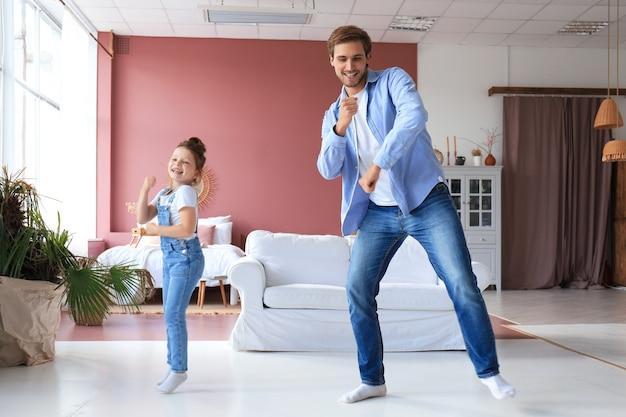 Jovem bonito dançando em casa com sua filha pequena e fofa.