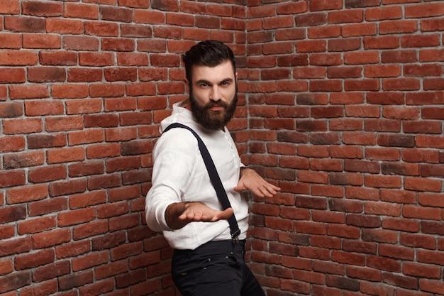 Jovem bonito dançando posando na parede de tijolo.