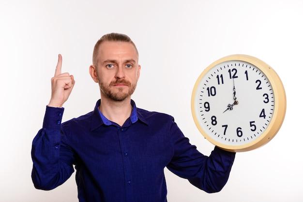 Jovem bonito de camisa azul com um grande relógio em pé apontando para cima