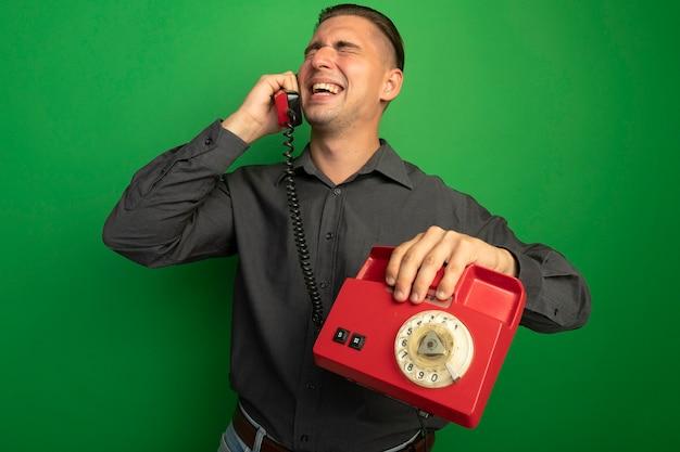 Jovem bonito de camisa cinza falando no telefone vintage e sorrindo alegremente em pé sobre a parede verde