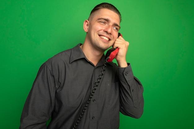 Jovem bonito de camisa cinza falando no telefone vintage e sorrindo alegremente