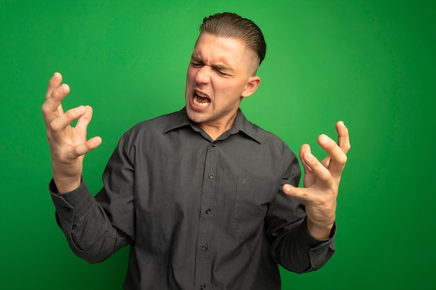 Jovem bonito de camisa cinza gritando e gritando com os braços abertos, louco, louco e zangado em pé sobre a parede verde