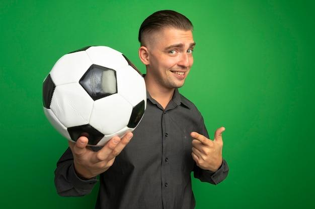 Jovem bonito de camisa cinza mostrando uma bola de futebol apontando com o dedo indicador para ela e sorrindo com uma cara feliz em pé sobre a parede verde