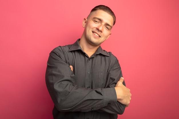 Jovem bonito de camisa cinza olhando para a frente com as mãos cruzadas sobre o peito sorrindo confiante em pé sobre a parede rosa
