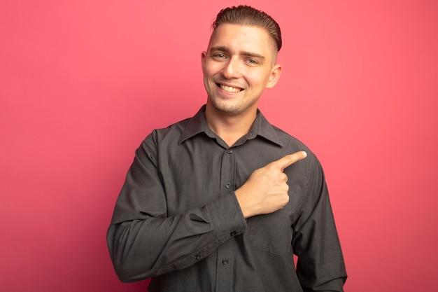 Jovem bonito de camisa cinza olhando para a frente sorrindo alegremente apontando com o dedo indicador para o lado em pé sobre a parede rosa