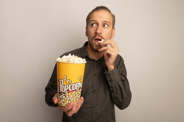 Jovem bonito de camisa cinza segurando um balde com pipoca e comendo, olhando de lado perplexo em pé sobre uma parede branca