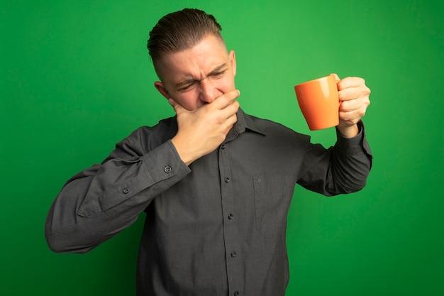 Jovem bonito de camisa cinza segurando uma caneca laranja, cobrindo a boca com a mão, sentindo desconforto em pé sobre uma parede verde