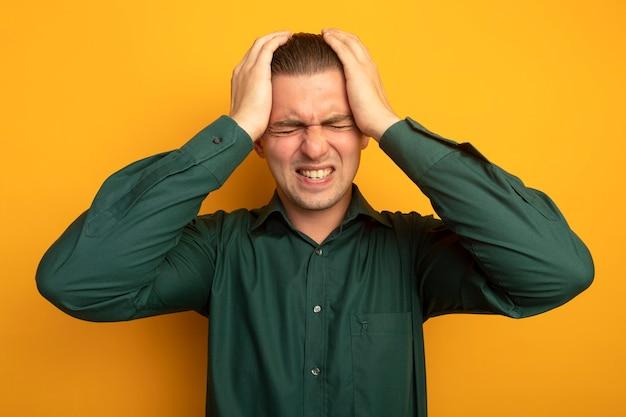 Jovem bonito de camisa verde segurando a mão na cabeça e sofrendo de forte dor de cabeça em pé sobre uma parede laranja